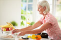 Middle aged woman cooking meal in kitchen by herself ingredients Royalty Free Stock Image