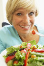 Middle Aged Woman Eating Healthy Salad Stock Photo