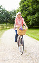 Middle aged woman enjoying country cycle ride with colourful flowers in basket Stock Images