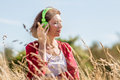 Middle aged woman enjoying quietness with music outdoors relaxation gorgeous listening to in headphones in dry high grass summer Stock Image