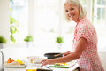 Middle aged woman following recipe on digital tabl tablet in kitchen smiling at camera Stock Photos