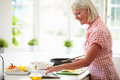 Middle aged woman following recipe on digital tablet in kitchen touching screen Royalty Free Stock Photo
