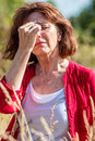 Middle aged woman having rhinitis allergies outdoors illness radiant with freckles hot flashes or hay fever reaction summer Stock Image