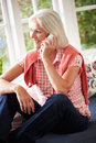 Middle aged woman at home talking on phone sitting down relaxing Stock Photo
