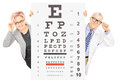Middle aged woman and a male optician standing behind eyesight t women test isolated on white background Royalty Free Stock Image