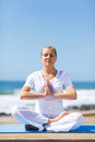Middle aged woman meditating portrait of calm outdoors on beach Stock Photography
