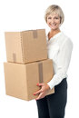 Middle aged woman moving packed boxes beautiful lady holding stack of parcel Royalty Free Stock Image