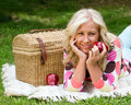 Middle aged woman on picnic holding apple while Stock Photos