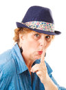 Middle aged woman putting her finger to her lips hushing gesture isolated white Stock Photos
