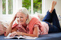 Middle aged woman reading magazine lying on sofa at home relaxing Royalty Free Stock Image