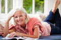 Middle aged woman reading magazine lying on sofa at home smiling to camera Royalty Free Stock Photo