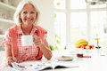 Middle aged woman reading magazine over breakfast smiling at camera whilst holding hot drink Royalty Free Stock Images