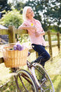 Middle aged woman relaxing on country cycle ride holding yellow flower smiling Royalty Free Stock Image