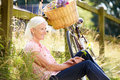 Middle aged woman relaxing on country cycle ride looking into distance smiling Stock Photo
