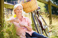 Middle aged woman relaxing on country cycle ride sitting down holding flower smiling Royalty Free Stock Photo