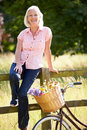 Middle aged woman relaxing on country cycle ride sitting fence smiling to camera Stock Images