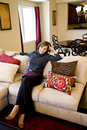 Middle-aged woman relaxing on living room sofa Stock Images