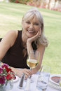 Middle aged woman sitting with wineglass at outdoor table portrait of a smiling caucasian a the Royalty Free Stock Image