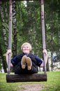 Middle aged woman swinging happy on a wooden swing with smile in her face Royalty Free Stock Images