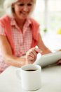 Middle aged woman using digital tablet over breakfast with hot drink in foreground Royalty Free Stock Image