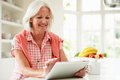 Middle aged woman using digital tablet over breakfast in kitchen with bowl of fruit in background Stock Photography