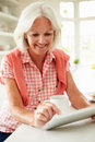 Middle aged woman using digital tablet over breakfast touching screen sitting at kitchen counter Royalty Free Stock Photos