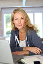 Middle aged woman working on laptop blond at home with Stock Photography