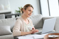 Middle aged woman working on laptop from home Stock Image