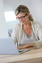 Middle aged woman working on laptop at home Stock Photography