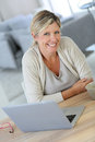 Middle aged woman working on laptop at home Royalty Free Stock Photo