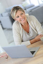 Middle aged woman working on laptop at home Royalty Free Stock Photography