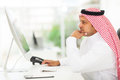 Middle eastern businessman looking on a computer screen sitting in his office Stock Photo