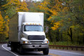 Middle size semi truck with box cargo on twisted highway Royalty Free Stock Photo
