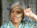 Middleage woman holding magnifier Royalty Free Stock Photography