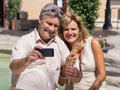 Middleaged mature couple posing for a self portrait eating ice cream romantic smiling on their smartphone as they enjoy refreshing Royalty Free Stock Photography