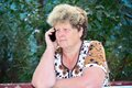 Middleaged woman talks on mobile phone the Royalty Free Stock Image