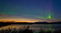 Midnight summer aurora borealis northern lights at in over horizon of lake laberge yukon territory canada at early dawn Royalty Free Stock Images