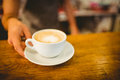 Midsection of barista serving heart shape frothy coffee at cafe Royalty Free Stock Photo