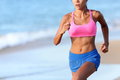 Midsection of determined woman jogging on beach young female is wearing sports bra and shorts sporty runner is exercising sunny Stock Photography