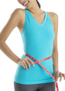 Midsection of fit woman measuring her waist in sports clothing against white background Royalty Free Stock Photography