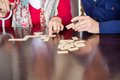 Midsection of grandmother playing dominoes with cropped image grandson in nursing home Stock Image