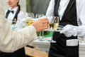 Midsection of professional waiter in uniform serving wine during buffet catering party, festive event or wedding. Full