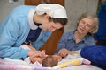 Midwife with baby a senior checks a newborn her mother Royalty Free Stock Image