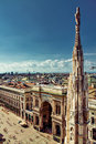 Milano city view and main square a over milan from the roof of the duomo with a gothic tower in the foreground piazza di duomo Royalty Free Stock Photo