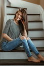 Miling Caucasian young beautiful woman model with messy long hair in ripped blue jeans and striped t-shirt Royalty Free Stock Photo