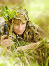 Military camouflaged man in forest with black handgun reading map Royalty Free Stock Photography