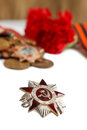 Military cap order of great patriotic war red flowers saint george ribbon isolated illustrative editorial vertikal shot with and Stock Photography