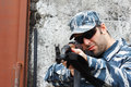 Military caucasian man in urban warfare aiming with grifle black sunglasses selective focus on face Stock Images