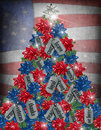 Military christmas tree dog tags and gift bows decorating a with textured flag background Stock Photos