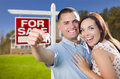 Military couple in front of home house keys and sign mixed race excited new with new for sale real estate outside Stock Photography
